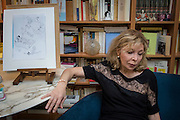 March 6, 2015, Paris, France. Widow Maryse Wolinski (1943, Algiers), in the livingroom of her Paris apartment, sitting beside the last completed drawing of Charlie Hebdo cartoonist Georges Wolinski (1934-2015) that seems to announce his death. After the Islamist terrorist attack on Charlie Hebdo, and her Husband's death, two month earlier, writer Maryse Wolinski deals with loss. The cartoonist Georges Wolinski was 80 years old when he was murdered by 2 French jihadists, he was one of the 12 victims of the massacre in the Charlie Hebdo offices on January 7, 2015 in Paris. Charlie Hebdo published caricatures of Mohammed, considered blasphemous by some Muslims. During his life, Georges Wolinski defended freedom, secularism and humour and was one of the major political cartoonists in France. The couple was married and had lived for 47 years together. Photo: Steven Wassenaar.
