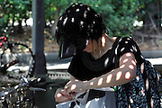 female in bicycle parking with light dots