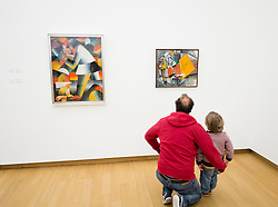 Man and boy looking at paintings at  Stedelijk Museum of contemporary art in Amsterdam The Netherlands