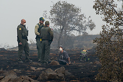 November 15, 2018 - Paradise, California, U.S. - Charlie Miles peers up at state forestry officers and state parks rangers after being arrested for trying to go home on a desolate stretch of Skyway Road between Paradise and a Chico church he has been sleeping since the fire started. The death toll from the Camp Fire in Northern California increased by one Sunday to 77, while the number of people unaccounted for has decreased to 993 people. The blaze was two-thirds contained as of Sunday night after consuming some 150,000 acres. (Credit Image: © Renee C. Byer/Sacramento Bee via ZUMA Wire)