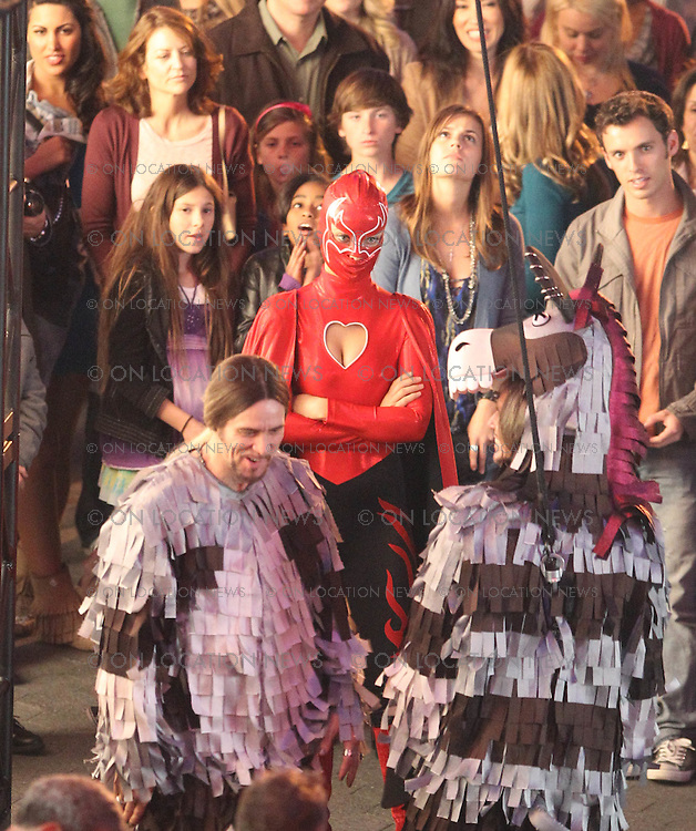 """January 26th 2012 Los Angeles, CA. Non Exclusive. Olivia Wilde in a superhero costume and Jim Carrey as a Zebra Piñata, film a funny street magic performance scene for the film """"The Incredible Burt Wonderstone"""". Also in the scene was Steve Carell, Steve Buscemi & Alan Arkin. In the scene a volunteer picked from the crowd continually hits Jim Carrey with a baseball bat.The Magic gag is that Carrey suddenly disappears and the piñata breaks open and candy falls onto the amazed crowd. Filming took place at Universal Studios City Walk. Photo by Eric Ford / On Location News 1/818-613-3955 info@onlocationnews.com"""