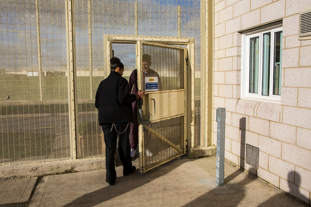 A prisoner is let back onto his wing by a prison officer. HMP/YOI Portland, Dorset. A resettlement prison with a capacity for 530 prisoners. Dorset, United Kingdom.