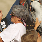 Julie Lotz, from Canmer, Ky., took a photo as school children petted some Arabian horses after their performance in the Equine Village Arena during the Alltech FEI World Equestrian Games at the Kentucky Horse Park on Thursday, October 7, 2010. After each performance, members of the audience had the opportunity to talk to the riders, trainers, and touch the horses. Photo by David Stephenson