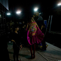 BEIJING, MAY -7, 2012 :  a model is led to the catwalk by helpers. . .Guo Pei , 45, is China's answer to haute couture. When she started out 15 years ago, there was no fashion in China .  Since then though  about everything in China has changed. Many more people are able to afford luxury products, and Chinese women, at least those who can afford it, follow international fashion trends. What makes Guo Pei different is what she puts on a runway. She employs 300 people in a workroom two hours from Beijing. She had to train them, but it?s also true that her creative freedom is tethered to relatively cheap labor. One dress alone, made entirely of golden panels, took 50,000 hours to embroider.