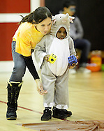 Middletown, New York  - A volunteer helps a young child in a costume play games in the gymnasium during the Middletown YMCA Family Fall Festival on Oct. 29, 2011.