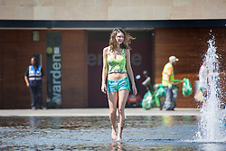 © Licensed to London News Pictures. 30/06/2015. Bradford UK. A young woman cool's off in the water fountains at Centenary square in Bradford. Britain is set to sizzle in temperatures of up to 34C (93F) today, with forecasters predicting the hottest day for several years. A tropical air mass moving from North Africa, Spain and Portugal means that we could be hotter than Rio de Janeiro. Photo credit : Andrew McCaren/LNP