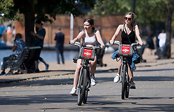 © Licensed to London News Pictures. 10/08/2020. London, UK. Two women riding bikes in the warm weather Hyde Park in London at the start of a week in which more warm weather and thunderstorms are forecast. Photo credit: Ben Cawthra/LNP