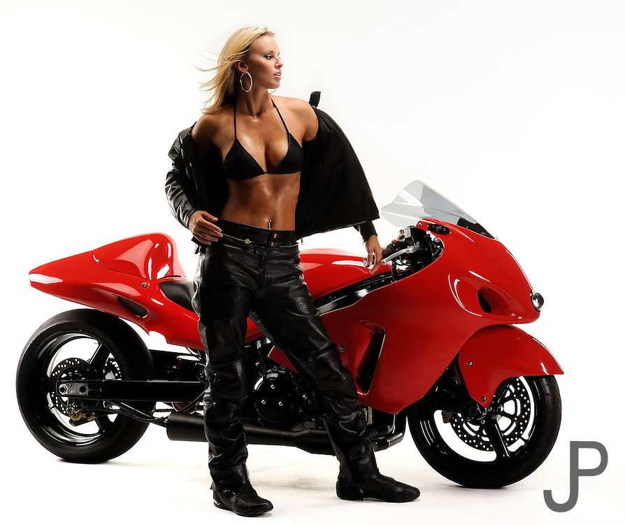 Emily Cochran in racing leathers standing in front of 2006 Hayabusa drag racing motorcycle with wind in her face.  No logos, model and property released.