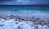 Wintertime scenery of covered with snow pebbles on a shore of Georgian Bay. Bruce Peninsula National Park, Ontario, Canada.
