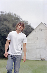 hot guy walking by a rustic barn in rural America