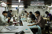 Small workshops is everywhere, tucked away In small lofts or in narrow alleys. To get into this sewing workshop, you have to climb a ladder against the wall and wiggle your way through a two feet gap.