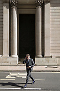 A business man walks beneath the high outer walls of the Bank of England in the City of London, the capital's financial district, on 25th March 2019, in London, England.