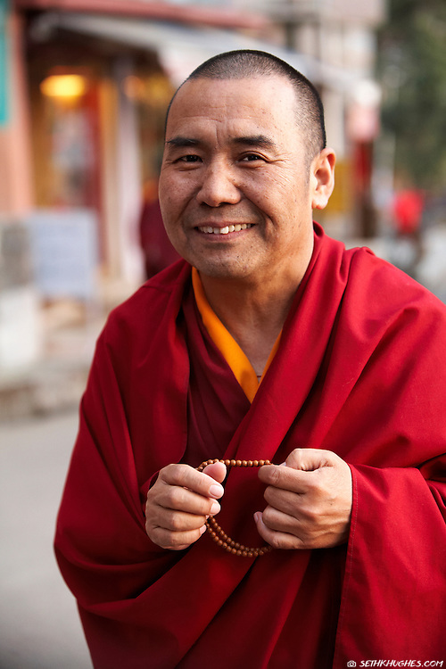 A Tibetan Buddhist monk with prayer beads walks in the street of McLeodGanj, Dharamsala, India.