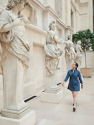 Woman looking at sculptures at the Louvre museum in Paris France