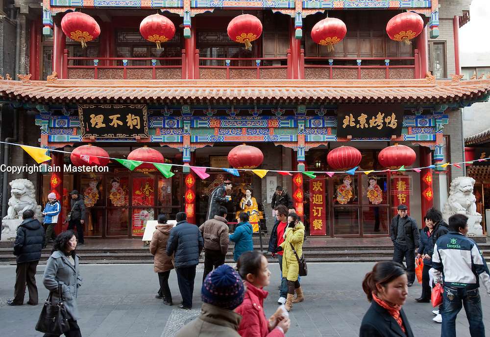 Busy street and traditional roast duck restaurant in historic Dashilan district of Beijing in China