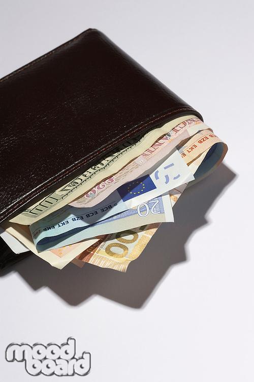 Wallet full of different currencies in studio