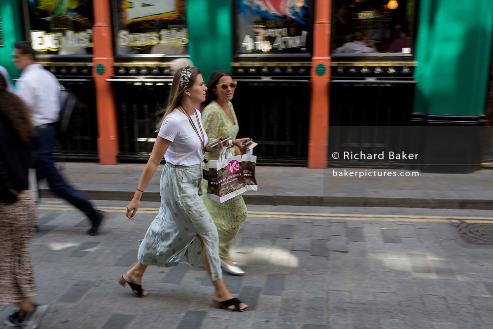Lunchtime women City workers carry their identical takeaway food packages along Watling Street (the former Roman thoroughfare) in the City of London, the capital's financial district (aka the Square Mile), on 22nd August 2019, in London, England.