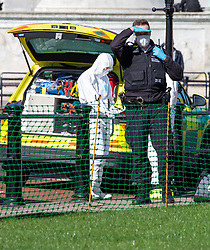© Licensed to London News Pictures. 16/03/2020. London, UK. Police and medics in masks outside Buckingham Palace today as they seem to be assisting someone in St James's Park as Government ministers warn that the over 70s could face self-isolation for weeks as the Coronavirus disease pandemic continues . Photo credit: Alex Lentati/LNP