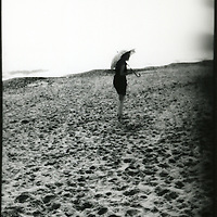 A young woman holding an umbrella walking along a sandy shore