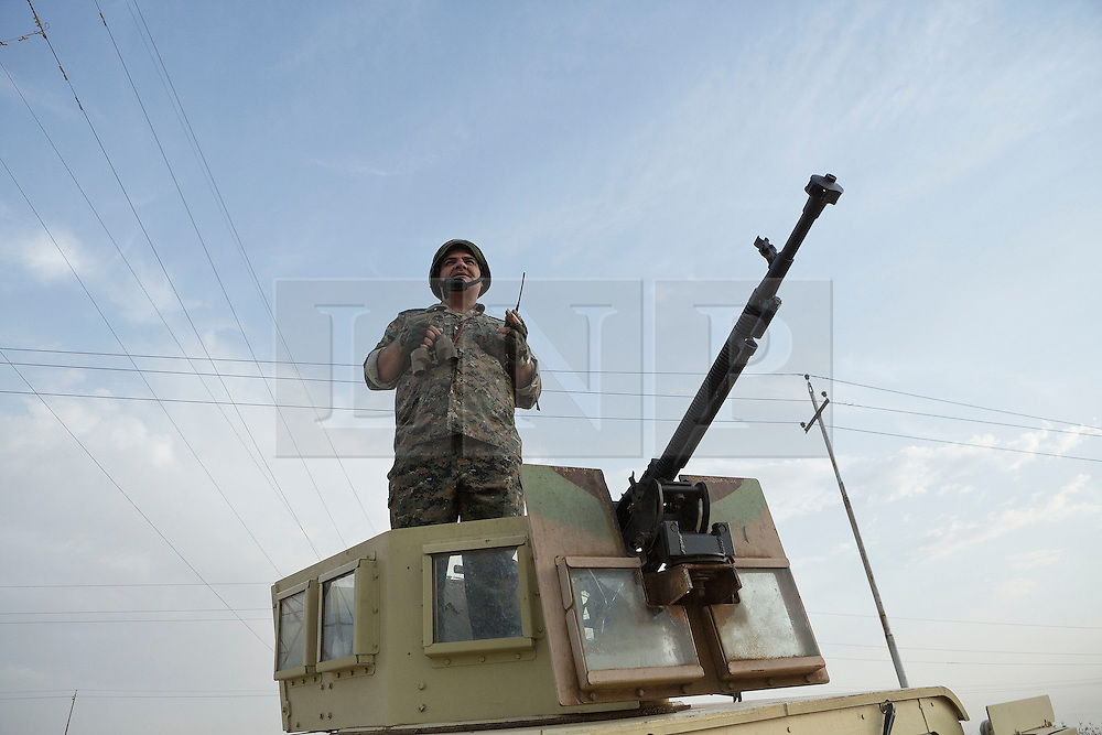 © Licensed to London News Pictures. 30/09/2015. Kirkuk, Iraq. A Kurdish peshmerga captain watches the start of a firefight from the turret of his armoured Humvee vehicle during an offensive to re-take 11 villages in the Kirkuk area from the Islamic State.<br /> <br /> Supported by large amounts of coalition airstrikes, members of the Iraqi-Kurdish peshmerga today (30/09/2015) took part in an offensive to take seven villages across a large front near Kirkuk, Iraq. By mid afternoon the Kurds had reached most of their objectives, but suffered around 10 casualties all to improvised explosive devices. All seven villages were originally Kurdish and settled with other ethnic groups during the Iraqi Arabisation process of the 1970's and 80's. Photo credit: Matt Cetti-Roberts/LNP