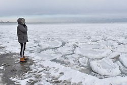 © Licensed to London News Pictures. 31/12/2017. CHICAGO, USA.  A tourist looks at pancake ice which has formed in the waters of Lake Michigan around Chicago during a period of sub-zero temperatures.  Extremely cold conditions are forecast to continue into the New Year. Photo credit: Stephen Chung/LNP