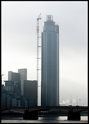 The remains of a construction crane hang from St Georges Wharf in Vauxhall, on January 16, 2013 in London, England. According to reports, a helicopter hit the crane on St Georges Wharf Tower before plunging into the road below during the morning rush hour., Wednesday January 16, 2013. Photo By Andrew Parsons / i-Images