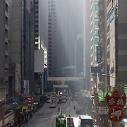 Des Voeux Road and traffic in morning sun in Central district. Pedestrians cross the road between tall buildings with trams and busses waiting at red lights. 7 million people live on 1,104km square, making it Hong Kong the most vertical city in the world.
