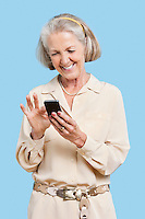 Smiling senior woman reading text message on cell phone against blue background