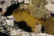 Dr. Jaime Bosch in search of the Majorcan midwife toad (Alytes muletensis). This pond is the habitat for the Majorcan midwife toad (Alytes muletensis) Torrent de s'Esmorcador, Majorca, Spain. | In dem Tal Torrent de s' Esmorcador hoch oben in der Berglandschaft Mallorcas finden sich kleine Felstümpel - das Laichhabitat der Mallorca-Geburtshelferkröte (Alytes muletensis). Die Kaulquappen werden eingefangen und in das Marineland Aquarium in Las Palmas gebracht. Dort werden sie einer fünftägigen Behandlung gegen die weltweit auftretende Pilzerkrankung unterzogen, bevor sie per Hubschrauber wieder in ihr Gewässer entlassen werden.