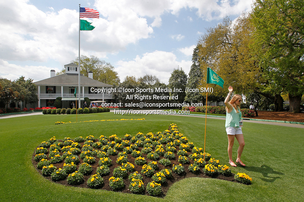 April 8, 2013 - Augusta, GA, USA - A patron poses for photos next to the Masters logo in flowers at Founders Circle in front of the Augusta National clubhouse in Augusta, Georgia, during a practice round for The Masters, Monday, April 8, 2013