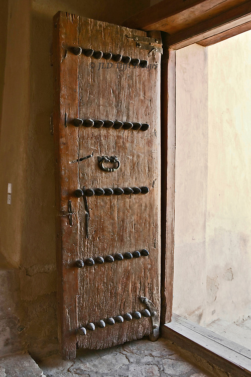 Heavy wooden door, studded with heavy iron studs, at the Al Rustaq fort in Oman.  It seems to urge us to go somewhere.  Or to come back.