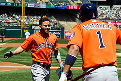 OAKLAND, CA - MAY 01:  Jose Altuve #27 of the Houston Astros is congratulated by Carlos Correa #1 after hitting a home run against the Oakland Athletics during the first inning at the Oakland Coliseum on May 1, 2016 in Oakland, California. (Photo by Jason O. Watson/Getty Images) *** Local Caption *** Jose Altuve; Carlos Correa