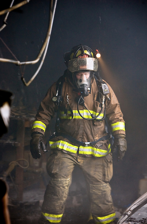 JEROME A. POLLOS/Press..A Kootenai County firefighter makes his way through debris after extinguishing flames inside a building at Ground Force Manufacturing.