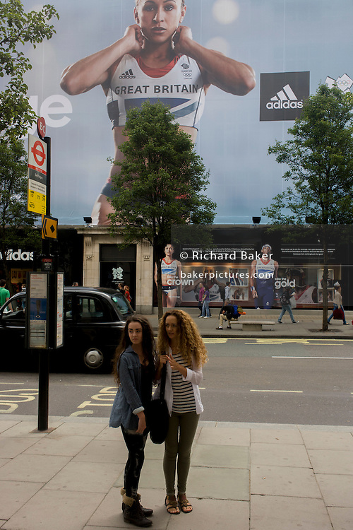 Two women window shop near the inspiring image of Team GB gold medallist heptathlete Jessica Ennis and long jumper Phillips Idowu which adorn the exterior of the Adidas store in central London's Oxford Street, during the London 2012 Olympic Games. The ad is for sports footwear brand Adidas and their 'Take The Stage' campaign which is viewable across Britain and to Britons who have been cheering these athletes who have been winning medals in numbers not seen for 100 years. Their heroic performances have surprised a host nation who until the victories, were largely anti-Olympics - now adoring their darling Ennis and her good looks.