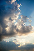 Rays of light shining through white clouds at sunset.