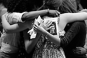 Connor Cook, 16, looks out from the program of his memorial service as his classmates Maia Lavoy, 15, left, Natalie Mitchell, 15, middle, and Aibhlin Moye-Linehan, 16, embrace in the Thetford Academy gym Saturday, July 7, 2012. Cook died June 27 after being struck by lightning four days earlier while working in the fields on Crossroads Farm in Post Mills. <br /> Valley News - James M. Patterson<br /> jpatterson@vnews.com<br /> photo@vnews.com