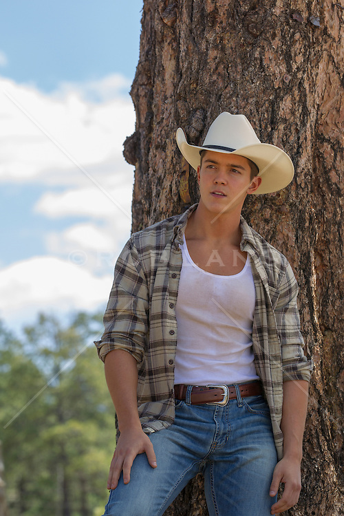 good looking young cowboy leaning against a tree