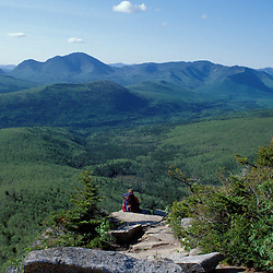 Backpacking. A hiker rests on Zeacliff  taking in the view of the Pemigewasset Wilderness.  The Twinway - Appalachian Trail.   White Mountains, NH