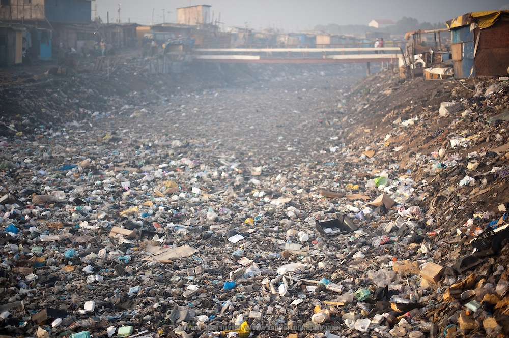 Beneath the muck and the haze from a nearby smoking dump lies the Odaw River, sluggishly carrying an untold volume of plastic waste, garbage and human excrement to the Korle Lagoon and on to the sea. On the low-lying lands along the river's edge is Old Fadama, Ghana's largest slum, home to some 80,000 people.