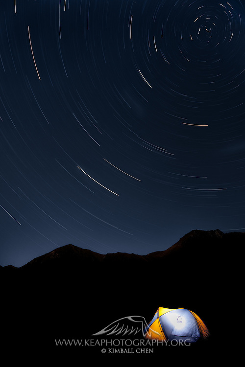 The stars here are rotating around the South Celestial Pole.  This campsite is on the shores of Green Lake in Fiordland, New Zealand. <br /> <br /> This long-exposure photograph was taken from 04:30am to 5:40am.  Moonlight illuminated the mountain range and lower-left third of the sky.