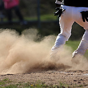 Dust flies at first base during the High School Baseball ball game between Trumbull Golden Eagles and McMahon Senators at Brien McMahon High School. Norwalk, Connecticut. USA. 26th April 2012. Photo Tim Clayton