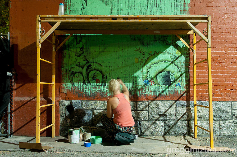Sarah Rachel works on her mural in the evening of August 11, 2016 during the Freak Alley Gallery sixth annual mural event in downtown Boise, Idaho.<br /> <br /> Sarah's mural is her take on a 70's kitsch forest scene that incorporates Idaho, but in her own way. <br /> <br /> Freak Alley Gallery's week long event provided an &quot;art-in-motion&quot; experience as it welcomed the public to watch artists work on their murals.