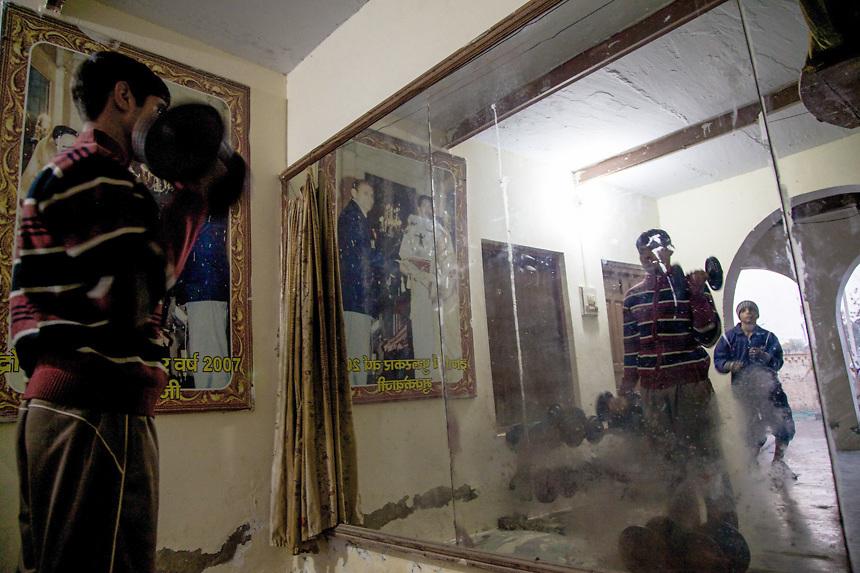 Un élève s'entraîne avec les poids devant le mirroir dans la cour du BBC (Bhiwani Boxing Club) de Bhiwani, école nommée The Little Cuba après avoir gagné une medaille aux Jeux Olympics de Pechin