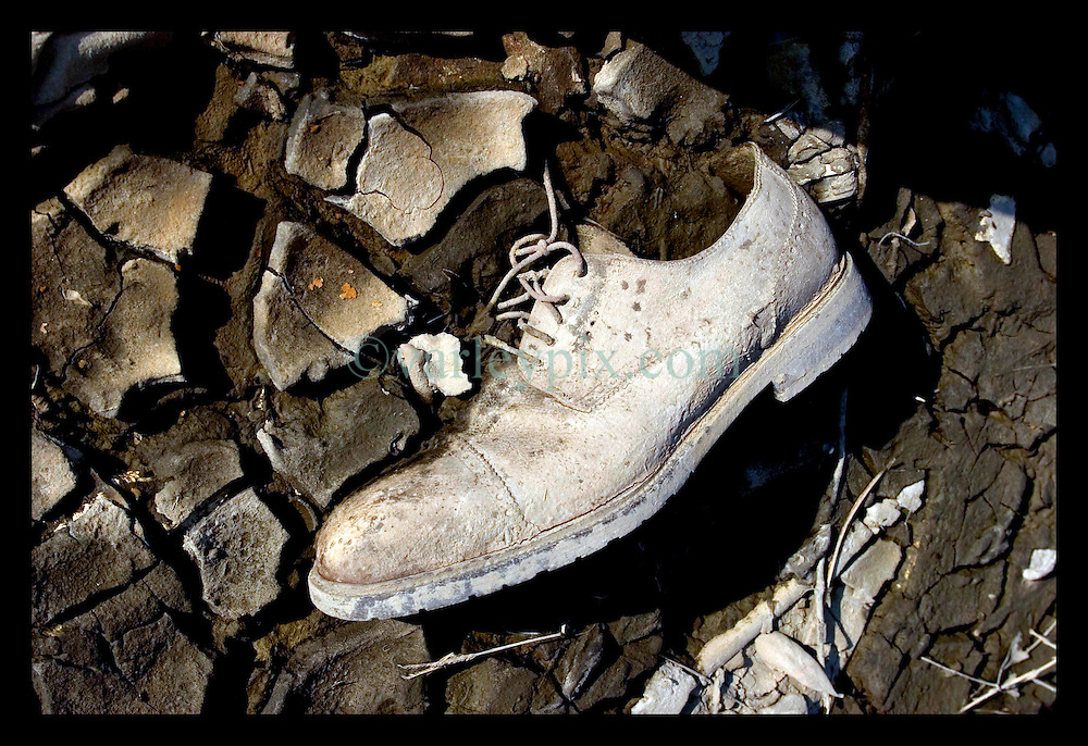 30th Sept, 2005. Hurricane Katrina aftermath, New Orleans, Louisiana. Lower 9th ward. The remnants of the lives of ordinary folks, now covered in mud as the flood waters remain. A man's shoe lies stuck in the mud.