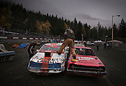 A crewman climbs over cars while cleaning windshields before the next race during Saturday night at the Races at Agassiz Speedway in Agassiz, BC (2012)