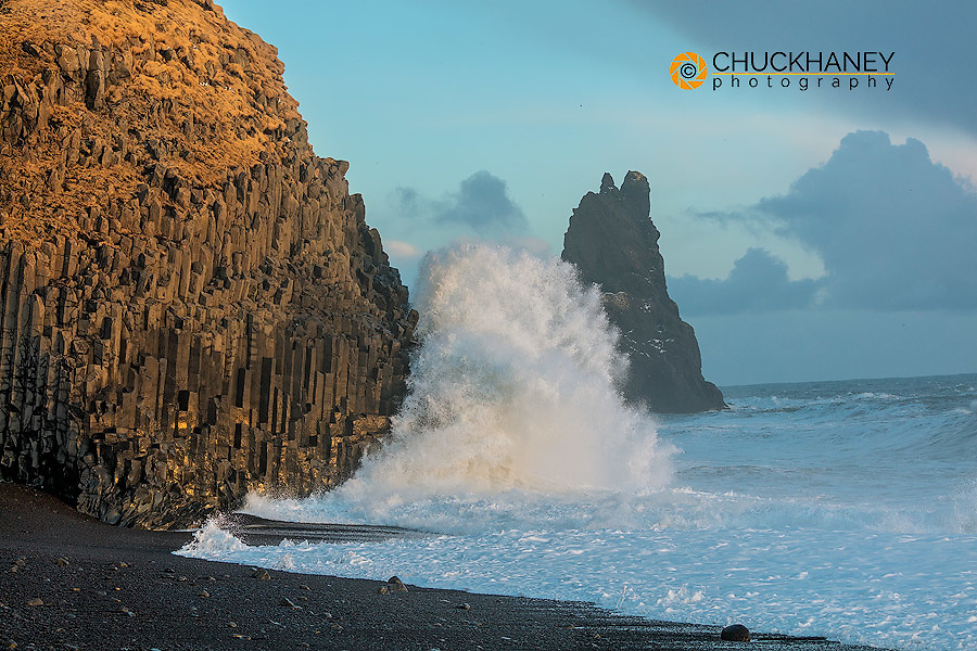 Waves from the North Atlantic Ocean crash into basalt columns at the Black Beach near Vik, Iceland
