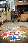 PUTTARPATHI, INDIA - 27th October 2019 - Lady stands infront of pookalam / rangoli pattern on floor at the entrance to her home in Puttarpathi, Andhra Pradesh, South India