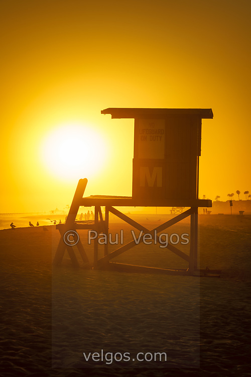 Lifeguard tower M at sunset photo in Newport Beach California. Newport Beach is a popular beach city in Orange County CA in the Western United States of America. Copyright ⓒ 2017 Paul Velgos with all rights reserved.