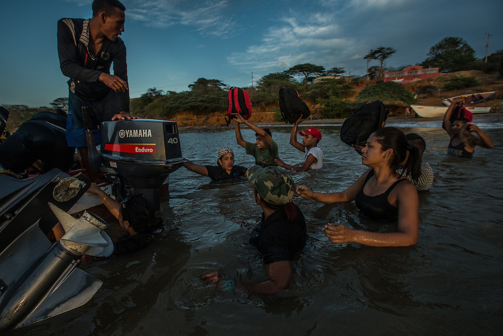FALCÓN, VENEZUELA - SEPTEMBER 26, 2016: Undocumented migrants board a smuggler's boat that will illegally take them from Venezuela to Curaçao. Undocumented migrants here have mortgaged property, sold kitchen appliances and even borrowed money from the same smuggling rings that pack them on the floorboards alongside drugs and other contraband. The journey to Curaçao takes them on a 60-mile crossing filled with backbreaking swells, gangs of armed boatmen and coast guard vessels looking to capture migrants and send them home. Then, after being tossed overboard and left to swim ashore, they hide in the brush to meet contacts who spirit them anew into the tourist economy of this Caribbean island. They clean the floors of restaurants, work in construction, sell trinkets on the street, or even solicit Dutch tourists for sex. But at least, the migrants say, there is food. PHOTO: Meridith Kohut