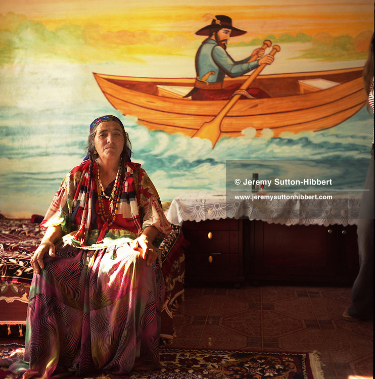 """An elder Roma woman, Sibinca,  sits on a bed infront of a nautical scene, depicting a """"pilgrim boatman"""" painted on the wall of her home, in the new part of the Sintesti Roma camp. Nautical scenes are very popular as wall decoration, but no-one within the camp knows the reason why they were first painted."""